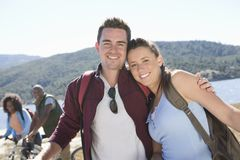 Couple With Friends In The Background At Lakeside Royalty Free Stock Photo