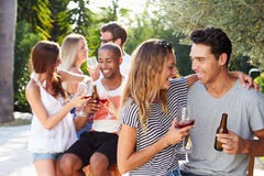 Couple With Friends Drinking Wine And Relaxing Outdoors Stock Photography