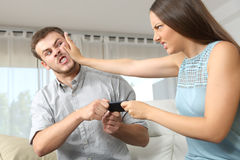 Couple or friends fighting for a mobile phone Royalty Free Stock Photo