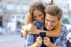 Couple or friends funny with a smart phone. Couple or friends laughing funny and having fun with a smart phone in a big city street Royalty Free Stock Photo