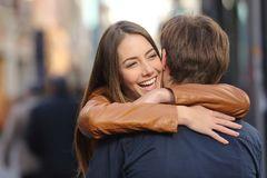 Couple of friends hugging in the street stock photography