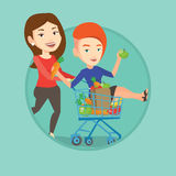 Couple of friends riding by shopping trolley. Stock Images