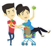 Couple of friends riding by shopping trolley. Royalty Free Stock Photos