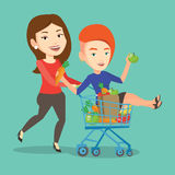 Couple of friends riding by shopping trolley. Royalty Free Stock Photography