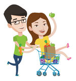 Couple of friends riding in shopping trolley. Stock Photography