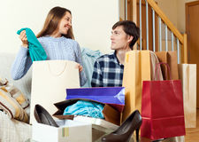 Couple friends smiling with bags after shopping. In home stock images