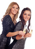 Couple of friends toasting with champagne in Christmas Royalty Free Stock Images