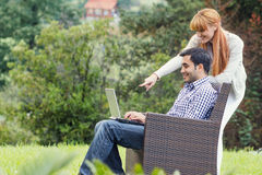 Couple or friends using laptop Stock Image