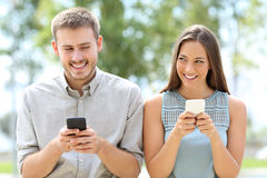 Couple or friends using smart phones. Front view of a couple or friends using smart phones and looking each other askance Stock Image