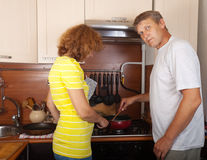 Couple fries meat. In her kitchen Royalty Free Stock Photos