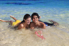 Couple frolic in the shallow tropical water. Young couple frolic in the shallow tropical water with a flower lei in hawaii Stock Photo