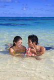 Couple frolic in the shallow tropical water Royalty Free Stock Photography