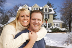 Couple in Front of Beautiful House with Snow on Ground Royalty Free Stock Images