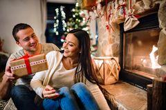 Couple in front of fireplace. Christmas time. Stock Photo