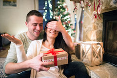 Couple in front of fireplace. Man givin present to woman. Stock Photos