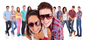 Couple in front of a  group of casual fashion people Stock Image