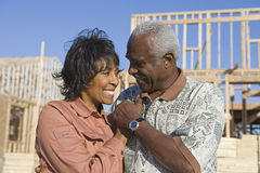 Couple In Front Of Incomplete House. Happy loving senior African American couple in front of incomplete house stock photography