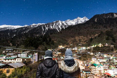 Couple in front of mountain with village in the night at Lachen in North Sikkim, India Royalty Free Stock Images