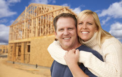 Couple in Front of New Home Construction Framing Site. Happy Excited Couple in Front of Their New Home Construction Framing Site Stock Images