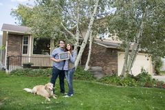 Couple in front of new home holding sold blackboard sign. Happy and excited New homeowners in front of new home with our first house sign Stock Photos