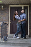 Couple in front of new home holding sold blackboard sign Stock Photos