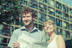 Couple on front of new house with blueprint project Royalty Free Stock Images