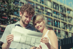 Couple on front of new house with blueprint project Stock Image