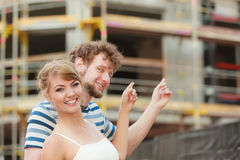 Couple on front of new house. Real estate. Real estate and family concept - young couple on front of new big modern house dreaming about home showing with royalty free stock images