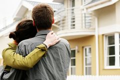 Couple in front of one-family house. In modern residential area