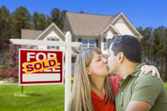 Couple in Front of Real Estate Sign and House. Happy Mixed Race Couple in Front of Sold Home For Sale Real Estate Sign and House stock photography