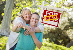 Couple In Front of Sold Real Estate Sign Holding Keys Stock Image