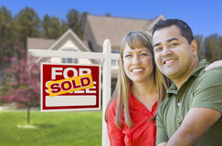 Couple in Front of Sold Real Estate Sign and House Royalty Free Stock Photography