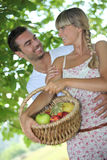 Couple with fruit basket Royalty Free Stock Photos