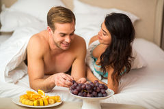 Couple with fruits in bed. royalty free stock photography