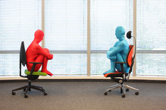 Couple in full body  elastic suits sitting on armchairs in sunny space Royalty Free Stock Images