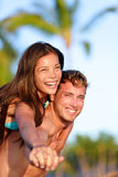 Couple fun on beach - man giving piggyback Royalty Free Stock Photo