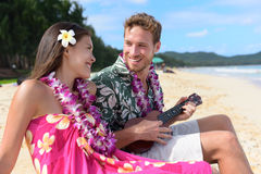 Couple fun on beach playing ukulele on Hawaii Stock Photography