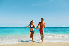 Couple Fun On Beach. Romantic People In Love Running At Sea Stock Photo