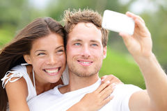 Couple fun taking self-portrait picture photos. With mobile smart phone or pocket camera outdoors. Happy multiracial young couple in love taking pictures Royalty Free Stock Image