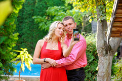 Couple fun taking self-portrait picture photos with mobile smart. Phone or pocket camera outdoors. Happy multiracial young couple in love taking pictures Royalty Free Stock Images