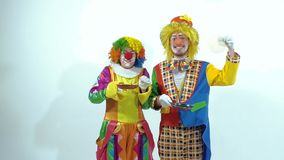 A couple of funny clowns holding small frying pans play with pancakes stock video