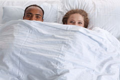 Couple with funny faces under the sheet. Royalty Free Stock Image