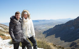 Couple in fur hood jackets against snowed mountainous valley Royalty Free Stock Images