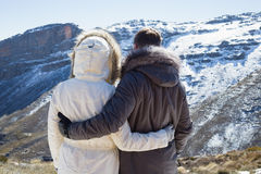 Couple in fur hood jackets looking at snowed mountain range Stock Photos