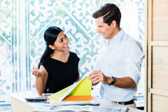 Couple in furniture store choosing material Royalty Free Stock Images