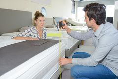 Couple in furniture store measuring bed. Measuring Stock Image