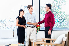 Couple in furniture store with shop assistant Stock Photos