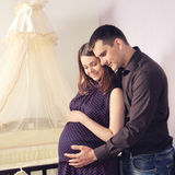 Couple future parents near a cot. Stock Image