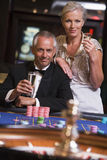 Couple gambling at roulette table. In casino Stock Photography