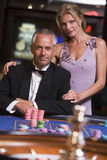 Couple gambling at roulette table Stock Images